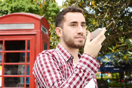 celphone: Portrait of young latin man sending voice messages. Outdoors. Urban scene. Stock Photo