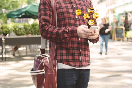 Close-up of man using smartphone sending emojis. Social concept. Foto de archivo