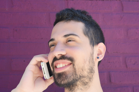 celphone: Portrait of young latin man talking on the phone against brick wall. Outdoors.