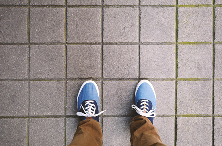Top view of casual shoes standing on asphalt city street.