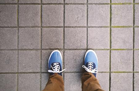 Top view of casual shoes standing on asphalt city street. Foto de archivo