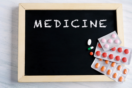 Close-up of empty chalkboard, pills and tablets. Healthcare concept.