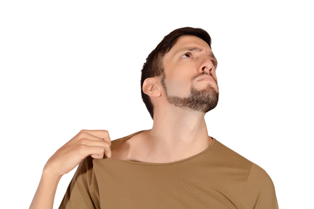 intolerable: Portrait of young man smelling his armpit. Isolated white background.