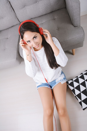 earbud: Beautiful young woman listening to music with headphones and relaxed. Indoors.