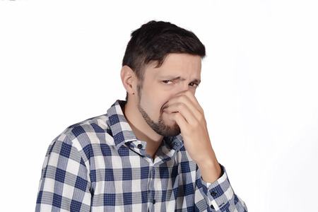 nuisance: Portrait of young man holding his nose against a bad smell. Isolated white background.