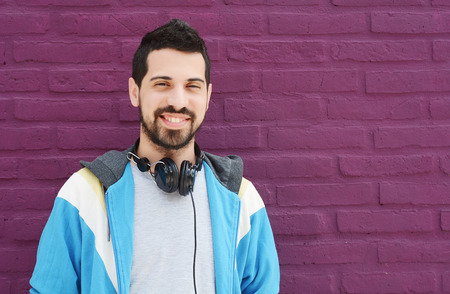 earbud: Portrait of young latin man listening to music with headphones. Outdoors.