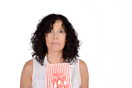 comfort food: Portrait of beautiful woman eating popcorn and watching movies. Isolated white background.