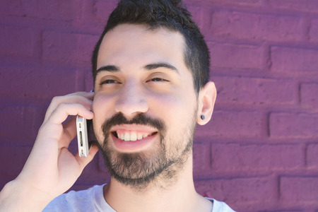 latinamerican: Portrait of young latin man talking on the phone against brick wall. Outdoors.