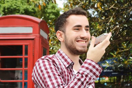 latinamerican: Portrait of young latin man sending voice messages. Outdoors. Urban scene. Stock Photo