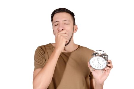 Portrait of young sleepy man with alarm clock. Isolated white background. Stock Photo