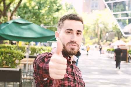 Portrait of young latin man doing ok gesture. Outdoors.