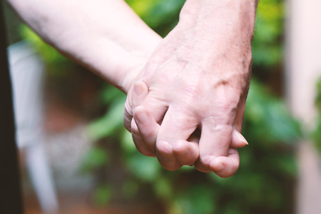 Close up of elderly couple holding hands outdoors.