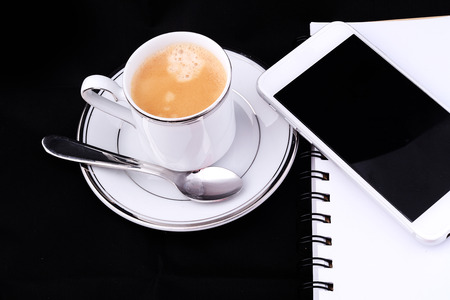 Close up of a cup of coffee with a notepad and smartphone. Stock Photo