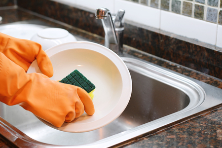 Close-up view of hands in rubber gloves washing dishes with sponge. Housework concept