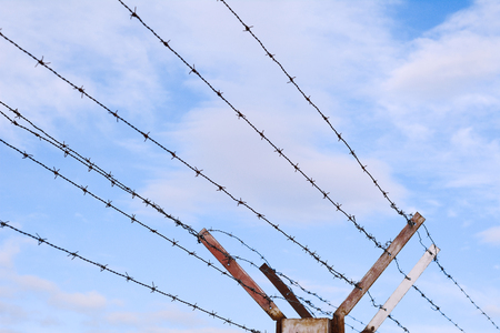Fence of barbed wire against blue sky with clouds.