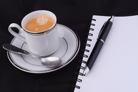 A cup of coffee with coffee capsule and a notepad on black background.
