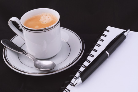 Close up of a cup of coffee with a notepad.