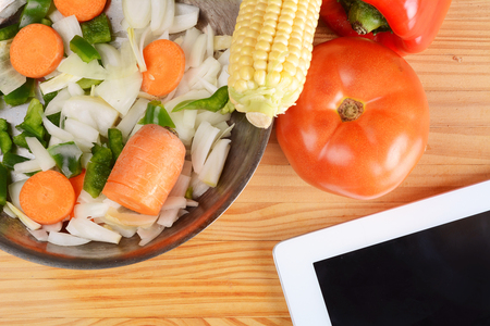 Vegetables and seasonings for cooking with a digital tablet on wooden table. Stock Photo