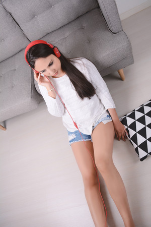 Beautiful young woman listening to music with headphones and relaxed. Indoors.