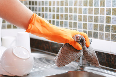 Hand with gloves wiping stainless steel sink with cloth. Housework concept