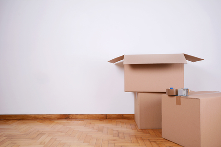 Stack of cardboard boxes in the empty room with copy space. Move concept