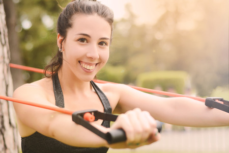 Portrair of young beautiful woman doing exercise at park. Sport concept. Outdoors Standard-Bild