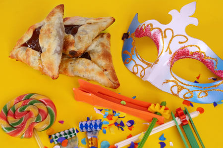 Top view of Purim background with carnival mask, party costume and hamantaschen cookies. Purim celebration concept