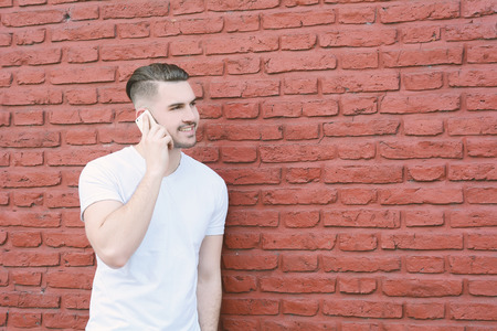 Portrait of young latin man talking on the phone against brick wall. Outdoors.