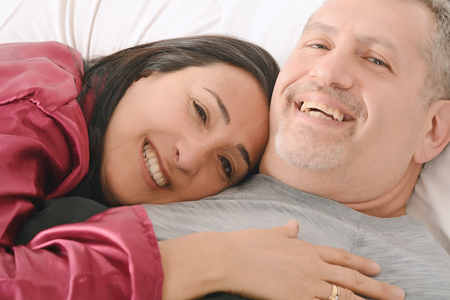 Middle-age couple in love relaxing together on their bed. Indoors