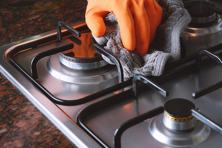 Close up view of hands in rubber gloves cleaning hob. Housework concept.