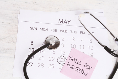 Stethoscope on calendar page. Regular medical examination concept.