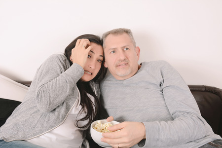Latin middle-aged couple laughing, eating popcorn and watching a scary movie together. Indoors