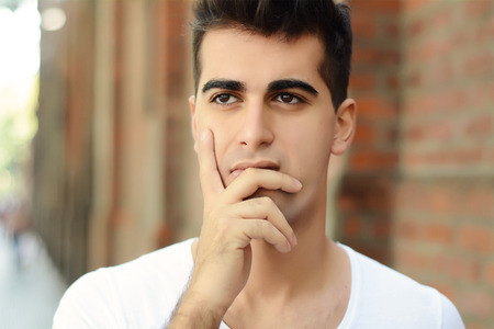 Portrait of handsome young thoughtful man. Outdoors