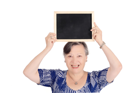 Elderly woman holding emty chalkboard in her hands. Isolated white background