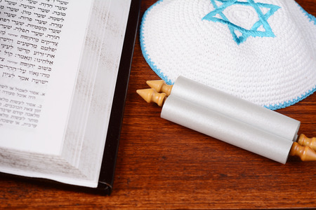 Torah with kippah on wooden background. Jewish religion concept Stock Photo