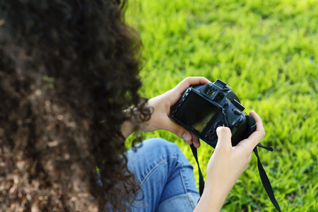 Young latin woman looking at photo camera in the park. Professional woman working. Outdoors