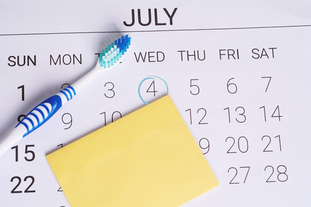 Calendar with a marked date and toothbrush to remind dentist appointment day in july. Dental hygiene and healthy concept.