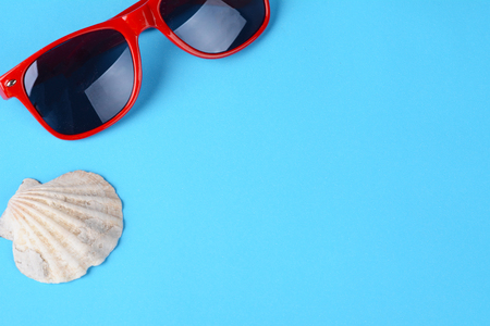 Top view of sunglasses and shell on Light blue background. Summer concept.
