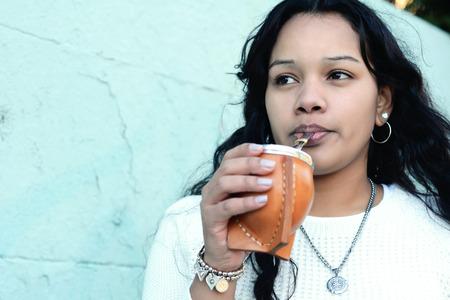 Porträt der jungen lateinischen Frau, die traditionellen argentinischen Yerba Mate Tee trinkt. Südamerikanisches beliebtes Getränk. Draußen