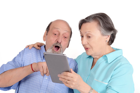 Shocked senior couple with tablet pc. Technology concept. Isolated white background
