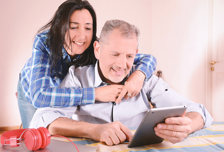 Couple using laptop at home. Pointing something. Indoors