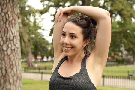 Portrair of young beautiful woman doing exercise at park. Sport concept. Outdoors Stock Photo