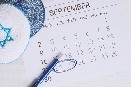 September calendar with kippah. Rosh Hashana, Yom Kippur and Sukkot. Jewish festivities concept.