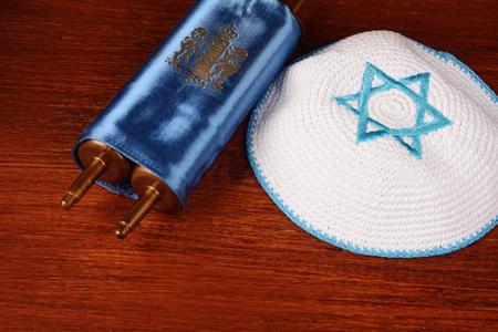 Torah with kippah on wooden background. Jewish religion concept Stock Photo