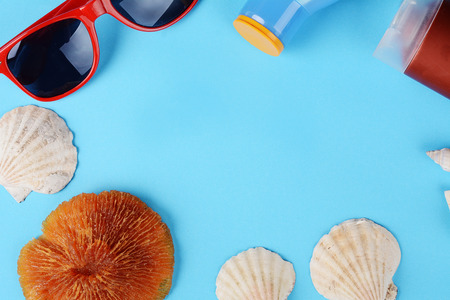 Top view of sunglasses, shells, starfish and sunblock with copyspace. Summer concept. Light blue background