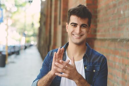 Felice giovane uomo sorridente guardando la telecamera e battendo le mani. Concetto di approvazione. All'aperto
