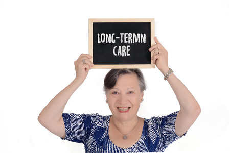 Elderly woman holding chalkboard with text