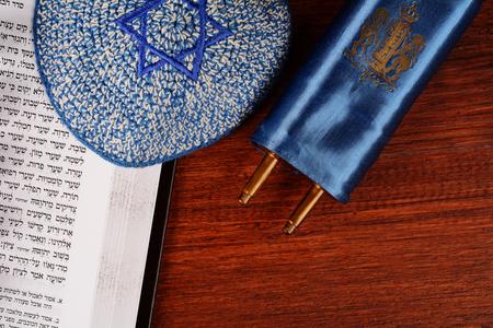 Torah with kippah on wooden background. Jewish religion concept Фото со стока