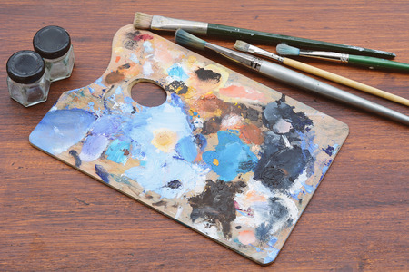 Artists palette with colorful oil paint strokes and paintbrushes on wooden background. Art concept Stok Fotoğraf