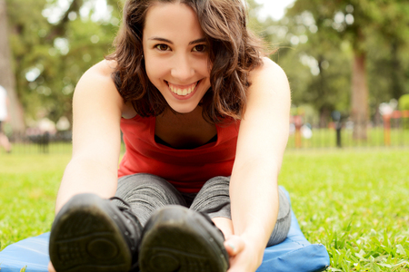 Portrait of young beautiful woman doing exercise at park. Sport concept. Outdoors Stock Photo